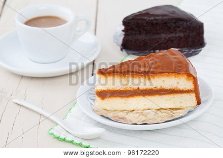 Coffee Cake On White Plate On Wooden Table With Coffee And Chocolate Cake