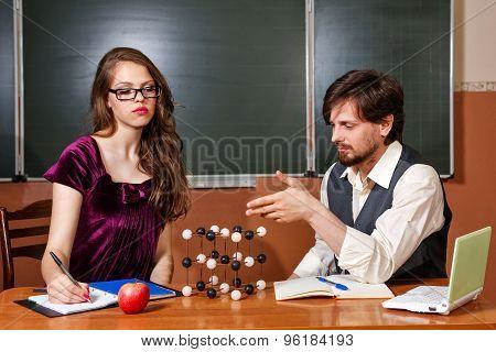 Teacher Explains Structure Of Crystal Lattice Of Student.