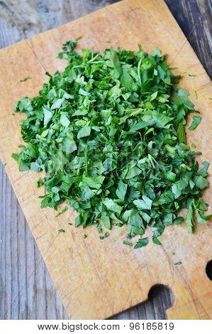 Chopped fresh green parsley on wooden board