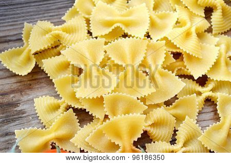 Uncooked butterfly shaped pasta farfalle on wooden table