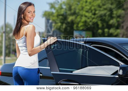 Attractive healthy girl is ready to sit down in car