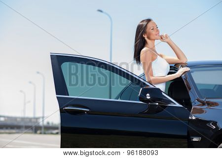 Beautiful young woman is waiting for her friend on road