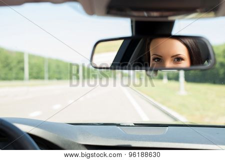 Cheerful young woman is driving her car