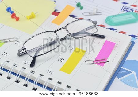 Glasses With Post It Notes And Pin On Business Diary Page