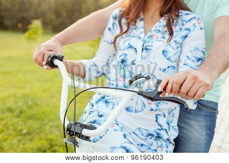 Young loving couple is riding bicycle in park