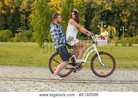 Cheerful young girlfriend and boyfriend are cycling