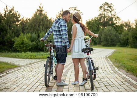 Pretty young loving couple is walking in park