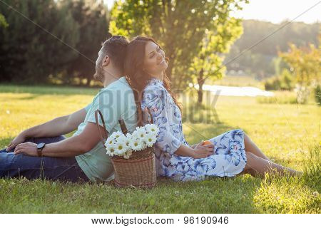 Cute young lovers are resting on the picnic