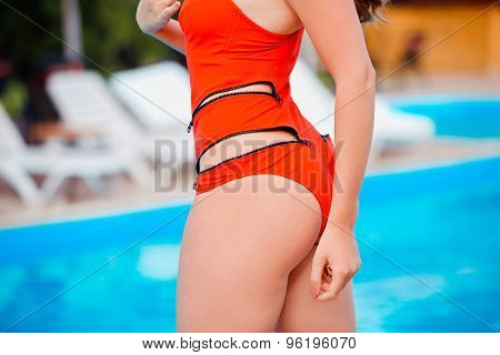 Perfect, sexy ass and buttocks of young woman wearing seductive red swimsuit