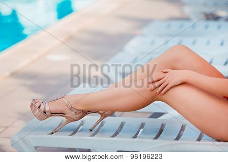 Perfect, sexy legs and ass of young woman relaxing on deck chair near swimming pool