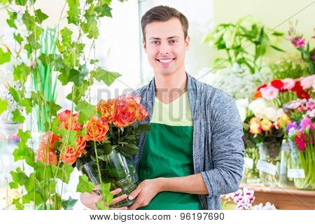 Young handsome florist selling flowers and bouquets in shop