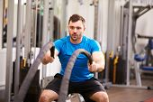 pic of battle  - Young man working out with battle ropes at a gym - JPG