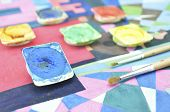 stock photo of messy  - Closeup of messy used water color paint box and paintbrush - JPG