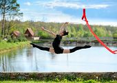 picture of leg-split  - Young gymnast girl doing exercise with red ribbon outdoor - JPG