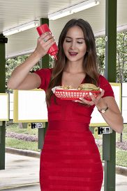 picture of squirt  - Woman squeezing a ketchup squirt condiment bottle on a bun - JPG