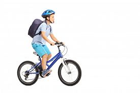 picture of schoolboys  - Studio shot of a schoolboy with a helmet and a blue backpack riding a bike isolated on white background - JPG