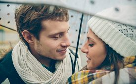 stock photo of rainy season  - Closeup of young beautiful couple looking at each other with love under the umbrella in an autumn rainy day - JPG