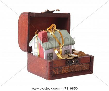 Wooden chest with coins and a small house