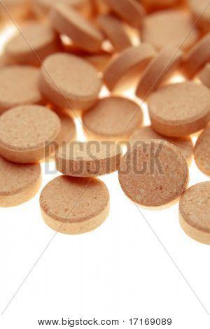 Vitamin tablets on plain background
