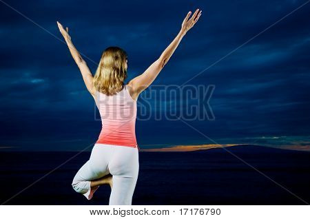 Woman Doing Yoga with Dramatic Sunset