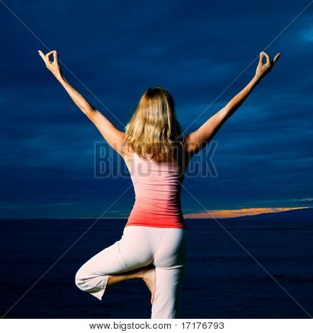 Woman Practicing Yoga in Front of Dark and Dramatic Sunset