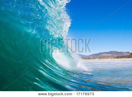 Blue Ocean Wave Breaks with Beach in Background