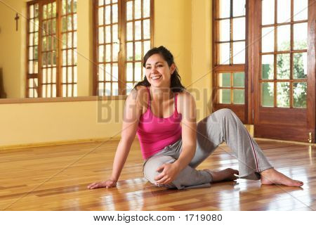 Healthy Young Woman In Gym Outfit Sitting On The Floor
