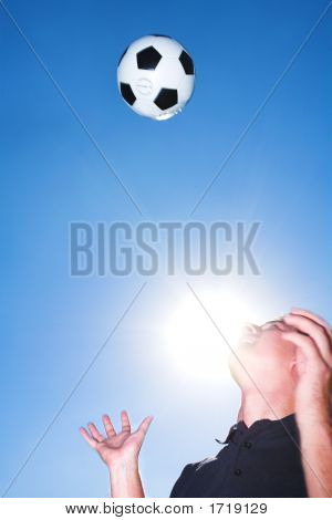 Soccer Player Or Coach And Ball Against A Blue Sky