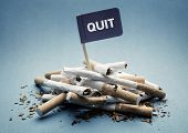 Quit or stop smoking concept pile of damaged cigarettes with sign poster