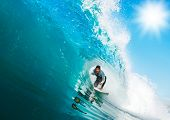 Surfer rides Big Wave, In the Tube with Sunny Blue Sky
