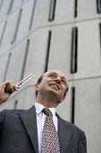 stock photo of tuning fork  - Businessman outside his office in the Central Business District with a tuning fork held to his ear indicating are you in tune with your business or its needs - JPG