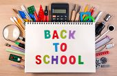 Back To School Text On Notebook Over School Supplies Or Office Supplies On School Table. Background poster