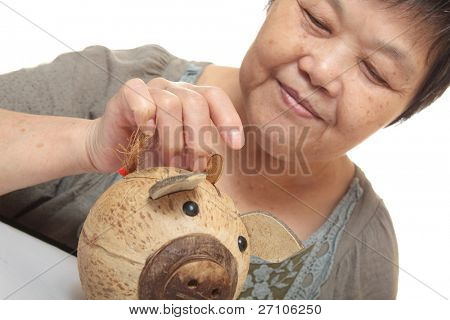 woman putting coins in small piggy bank. Selective focus, Copy space