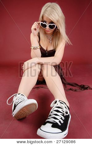 Smiling blonde sitting on a floor. Red background.