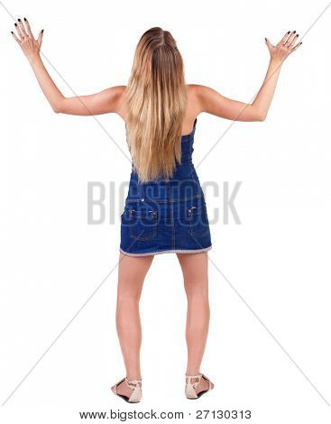 Back view of shocked and scared young beautiful woman. Holds hands upwards. Rear view. Isolated over white background.
