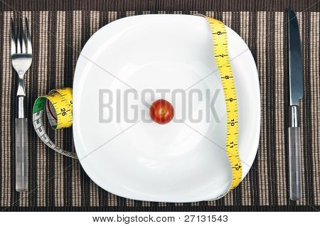 Cm ruler and small tomato on plate