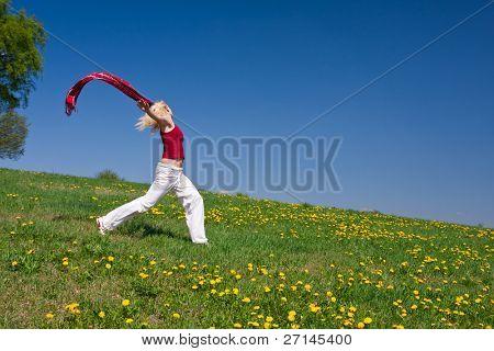 mujer joven con un pañuelo rojo en un prado en primavera