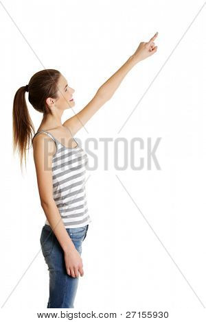 Site view portrait of a beautiful young female caucasian teen pointing up with her finger, on white.