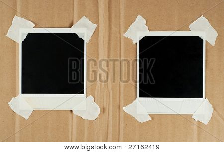 Two blank photo cards with masking tape on a cardboard