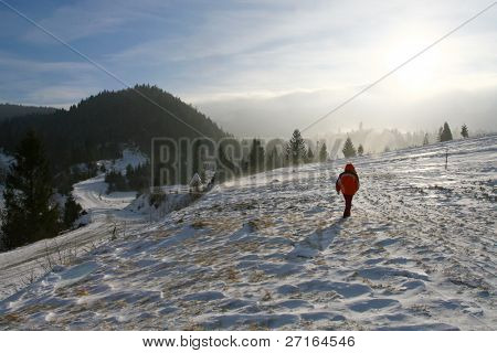 Beautiful winter mountain landscape with a man walking upon the snowy hill