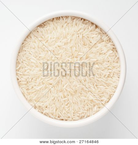 Uncooked basmati rice in a ceramic bowl on white background