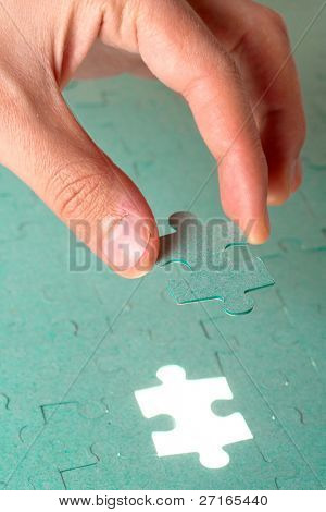 Hand inserting missing piece of green jigsaw puzzle into the hole