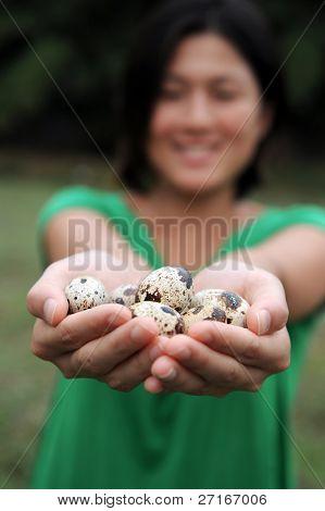 eine asiatische Mädchen lächelt wie sie ihre Handvoll Wachteleier wiegen