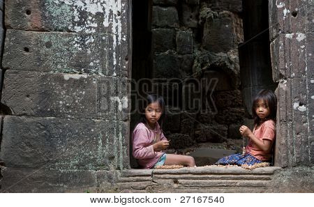 SIEM REAP, CAMBODIA - CIRCA JANUARY 2009: Two young girls make souvenir necklaces at Angkor Wat temple circa January 2009 in Siem Reap, Cambodia. Allegedly, children help to support their families.