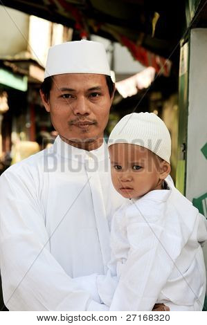 JAKARTA, INDONESIA - SEPTEMBER 20: A man and his son pose for a picture on their way to prayer at the mosque on Hari Raya, the end of a month of fasting called Ramadan September 20, 2009 in Jakarta.