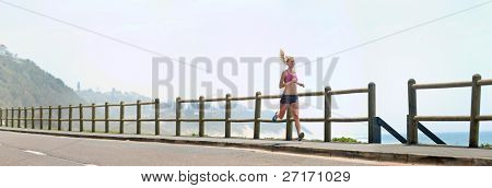 XXXL image - happy fitness running girl outdoors at the beach. Lots of copyspace provided