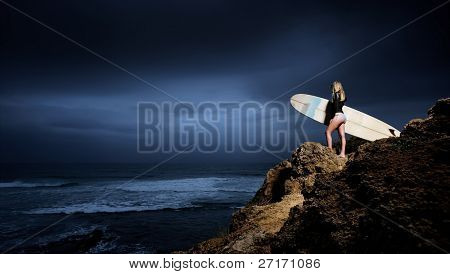 Young surfer holds her surfboard on cliff during stormy weather