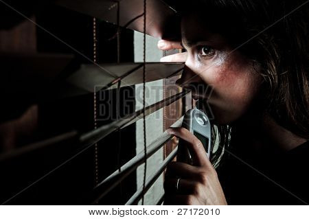 Fearful battered woman peeking through the blinds to see if her husband is home. she is contemplating whether to call the domestic violence hotline