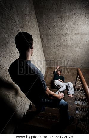 Battered woman lies lifelessly at the bottom of stairs, a conceptual shoot depicting the effects of domestic violence