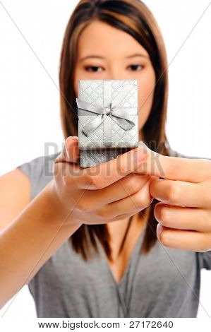 Attractive young woman opens a present, selective focus on giftbow